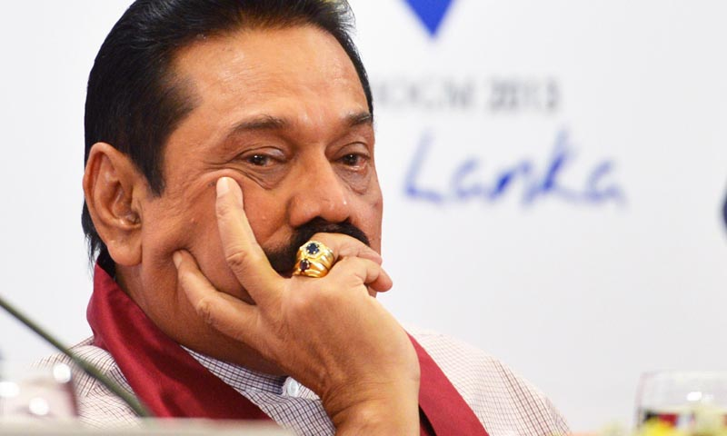 Sri Lanka President Mahinda Rajapaksa listens during a press conference during the Commonwealth Heads of Government Meeting (CHOGM) in Colombo on November 16, 2013.  Britain's David Cameron put Sri Lanka on notice to address allegations of war crimes within months or else he would lead a push for action at the UN.  AFP PHOTO/ISHARA KODIKARA